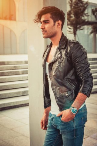 Stylish man in the white T-shirt, leather jacket and jeans standing near a column in modern architectural environment.